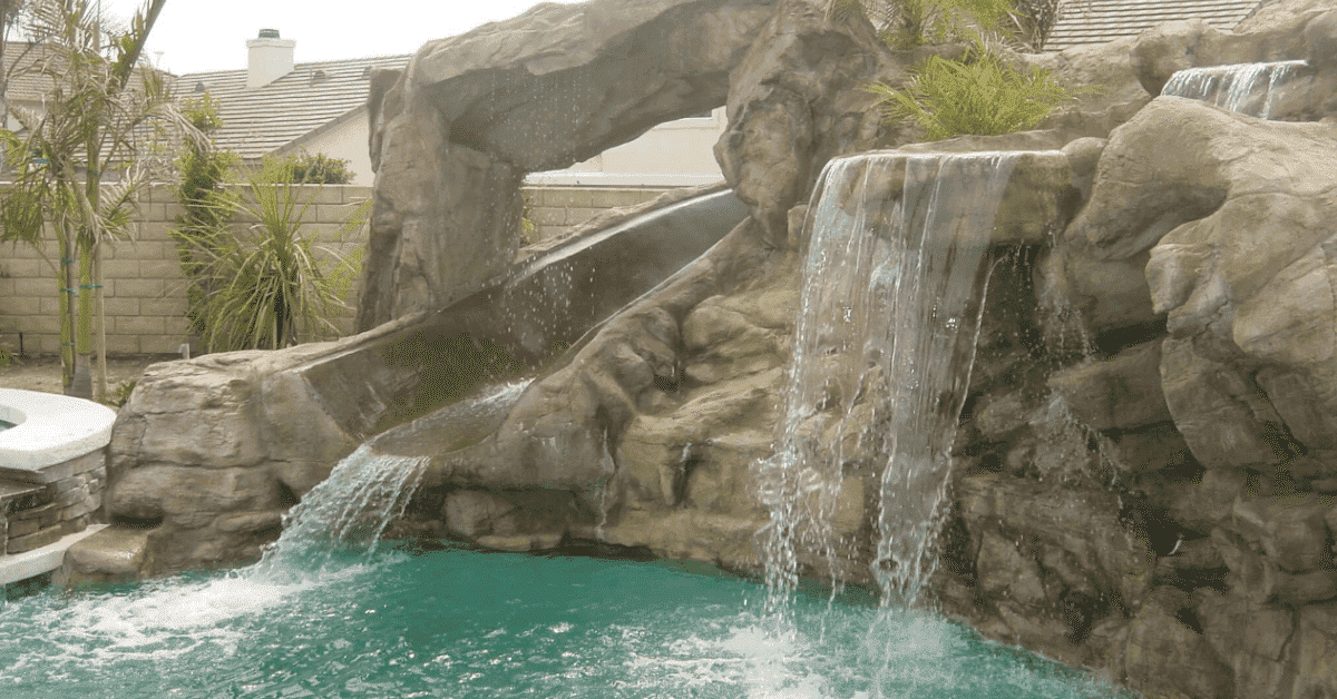 Swimming pool with a rock waterslide built by Thomas Pools.